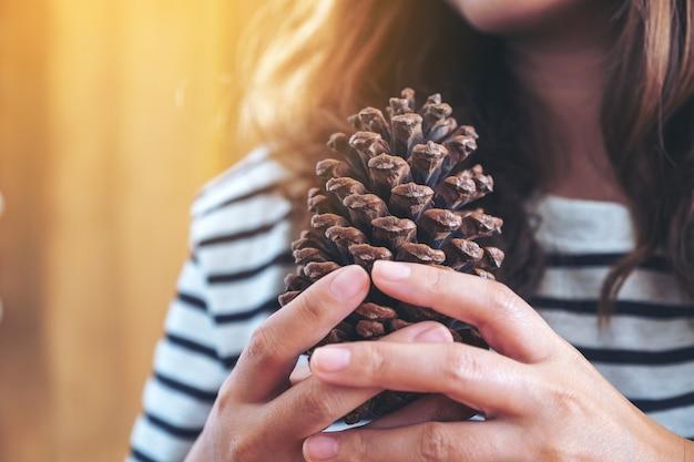 Imagem de close de uma mulher segurando uma pinha nas mãos