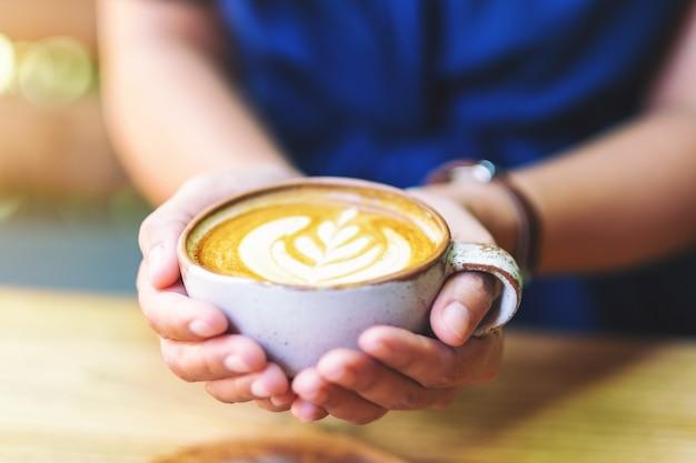 Imagem de close de uma mulher segurando uma xícara de café com leite quente na mesa de madeira