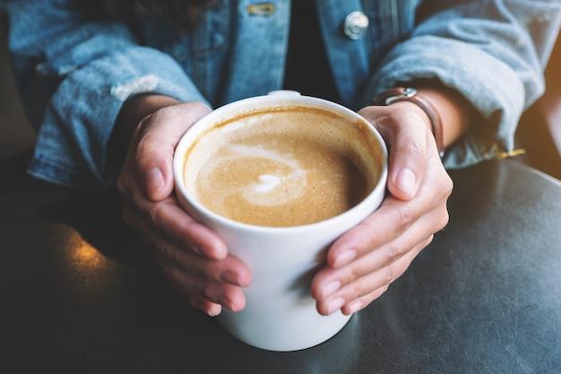 Imagem de close de uma mulher segurando uma xícara de café com leite quente na mesa