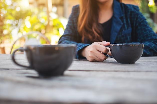 Imagem de close de uma mulher segurando uma xícara de café quente na mesa de madeira