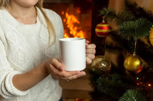Imagem de close de uma mulher sentada perto da lareira com uma xícara de chá