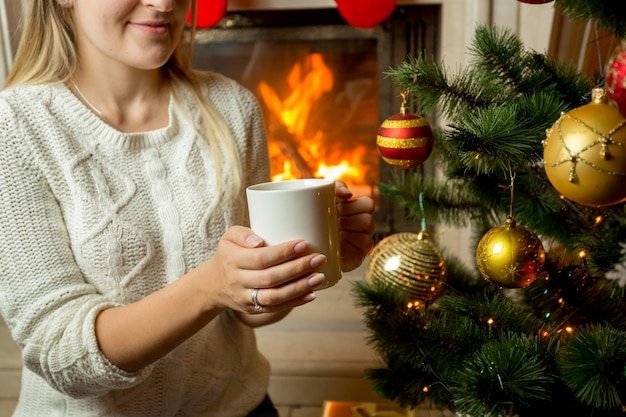 Imagem de close de uma mulher sentada perto da lareira e decorada uma árvore de natal com uma xícara de chá