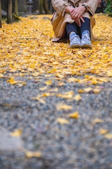 Imagem de close de uma mulher sentada sozinha na rua com cobertura de folhas amarelas de ginko no outono