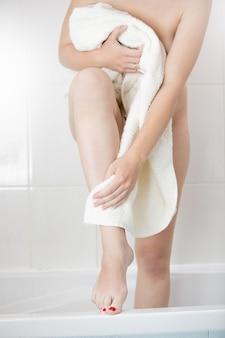 Imagem de close de uma mulher sexy enxugando as pernas com uma toalha