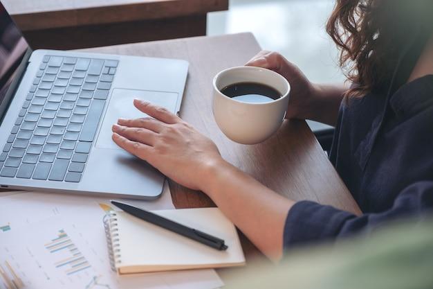 Imagem de close de uma mulher tocando no touchpad do laptop enquanto bebe café e trabalha no escritório