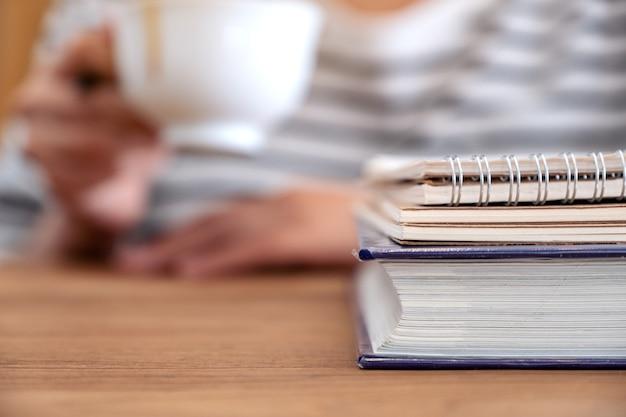 Imagem de close de uma mulher tomando café com livros e cadernos na mesa de madeira