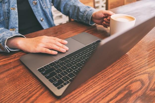 Imagem de close de uma mulher usando e tocando o touchpad do laptop na mesa de madeira enquanto bebe café