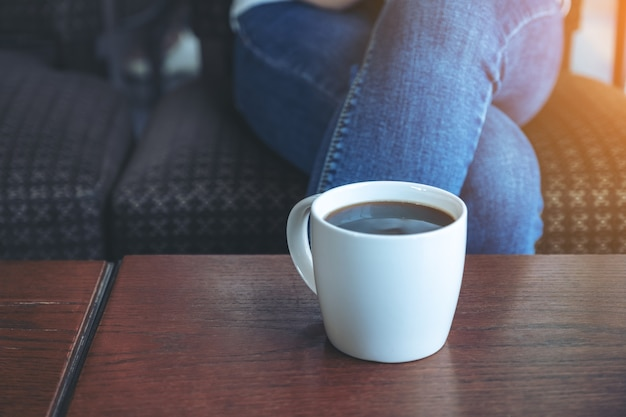 Imagem de close de uma xícara de café quente na mesa de madeira com uma mulher sentada no café