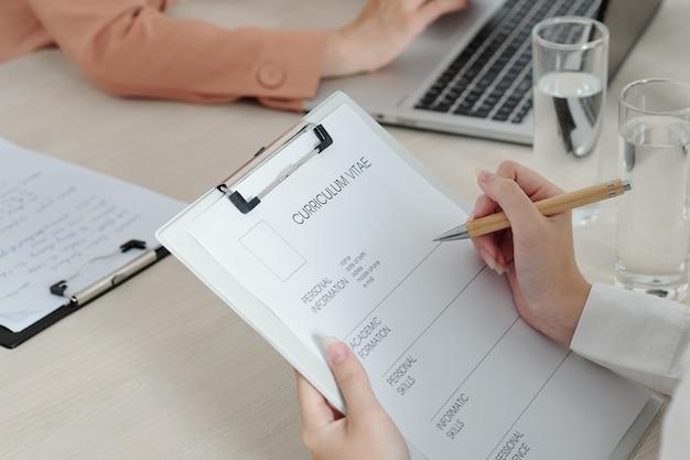 Imagem de close-up da candidata escrevendo suas informações pessoais e habilidades antes da entrevista de emprego