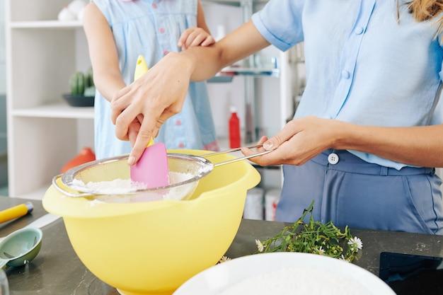 Imagem de close-up da mãe mostrando à filha pré-adolescente como peneirar a farinha quando estão fazendo massa