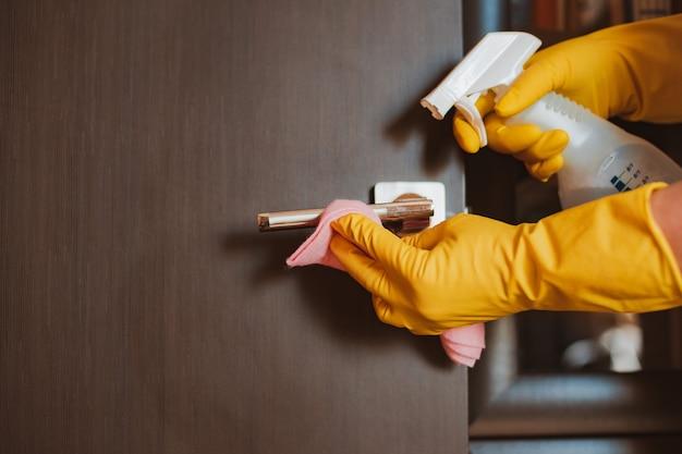 Imagem de close-up da mão de uma mulher em uma luva amarela usando um guardanapo para desinfetar e limpar a maçaneta da porta