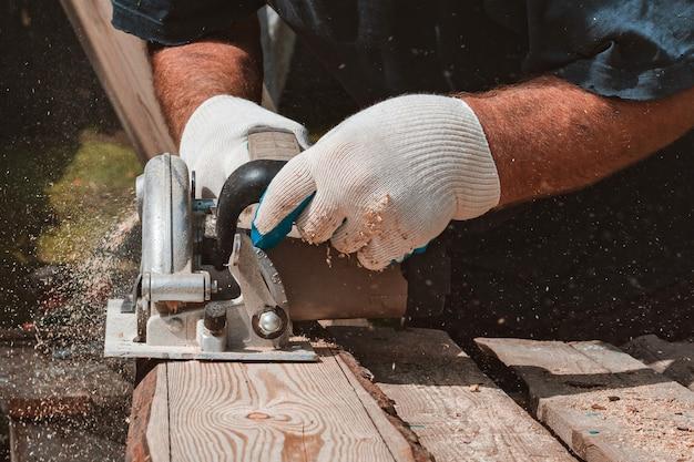 Imagem de close-up da mão irreconhecível do carpinteiro processando a placa de madeira na máquina de trabalhar madeira