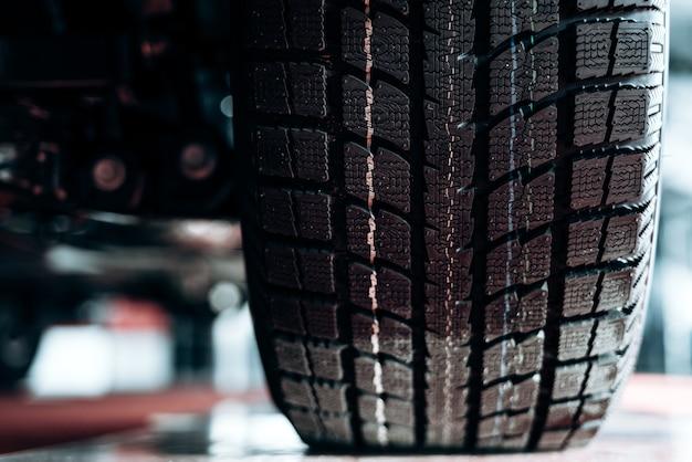 Imagem de close-up da roda do carro com pneu de borracha preto