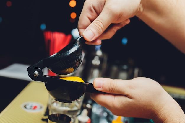 Imagem de close-up das mãos de um barman espremendo suco de limão em uma coqueteleira gelada no balcão do bar.