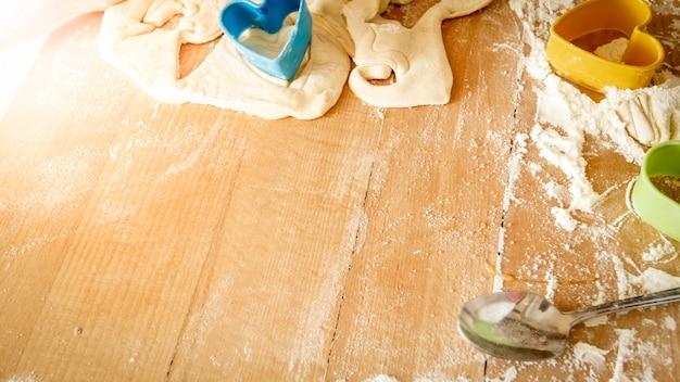 Imagem de close-up de alto ângulo em uma mesa de madeira coberta com farinha, massa, utensílios de cozinha e ingredientes para cozinhar e assar na cozinha