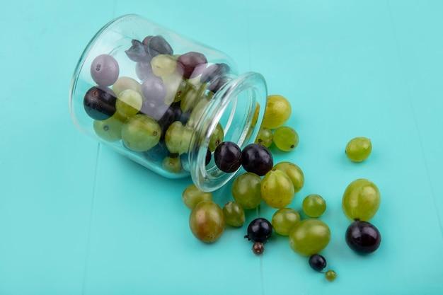 Imagem de close-up de bagos de uva caindo da jarra sobre fundo azul