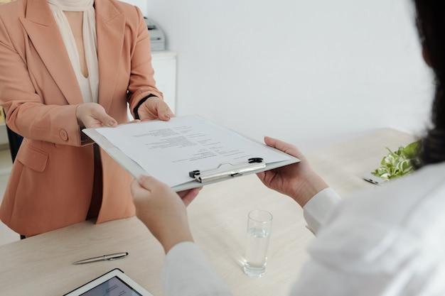 Imagem de close-up de candidata a emprego dando documento cv ao gerente de recursos humanos