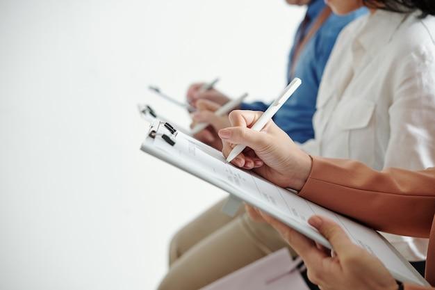 Imagem de close-up de candidatos escrevendo dados pessoais em cv quando sentados na fila