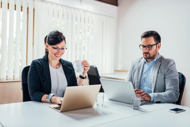 Imagem de close-up de dois parceiros de negócios bonita trabalhando em computadores portáteis.