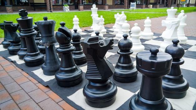 Imagem de close up de figuras de xadrez grandes em preto e branco para jogar no parque.