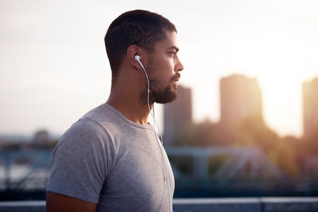 Imagem de close-up de jovem esportista em forma usando fones de ouvido, focando em seu treinamento