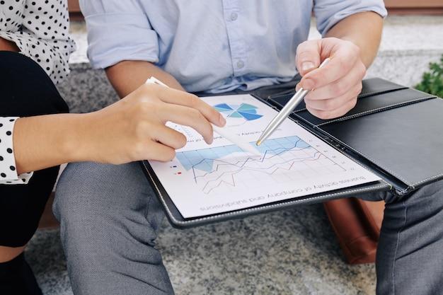 Imagem de close-up de jovens empresários apontando para o quadro financeiro e discutindo receitas e despesas