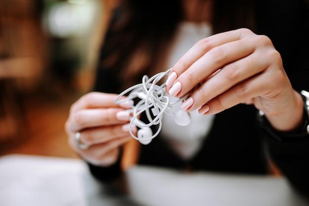 Imagem de close-up de mãos femininas segurando fones de ouvido emaranhados.