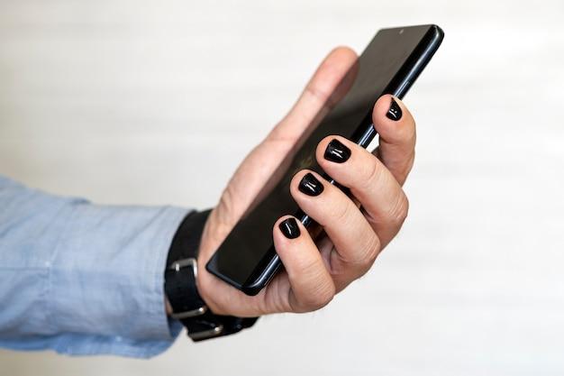 Imagem de close-up de mãos masculinas usando smartphone. à procura ou conceito de redes sociais, homem moderno digitando uma mensagem sms para seus amigos. homem com unhas pintadas. desenho de unhas masculinas. manicure dos homens.