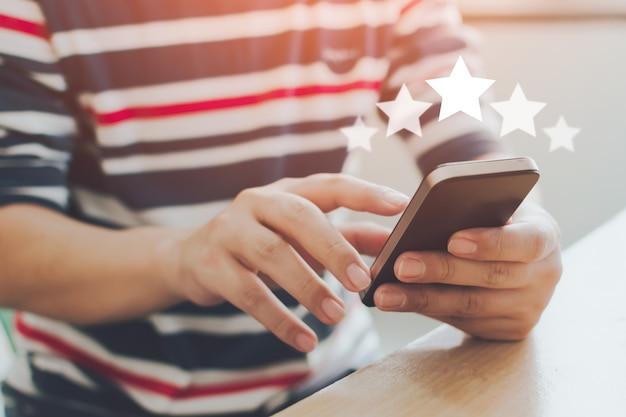 Imagem de close-up de mãos masculinas usando telefone móvel esperto com ícone de cinco estrelas