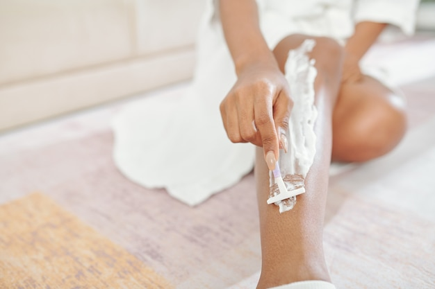 Imagem de close-up de mulher jovem em roupão de banho barbeando as pernas após tomar banho