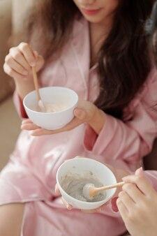 Imagem de close-up de mulheres jovens misturando argila em pó e água em uma tigela para aplicá-la como máscara facial mais tarde