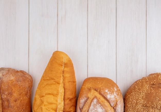 Imagem de close-up de pães como baguetes semeados de espiga marrom e crocantes em fundo de madeira com espaço de cópia