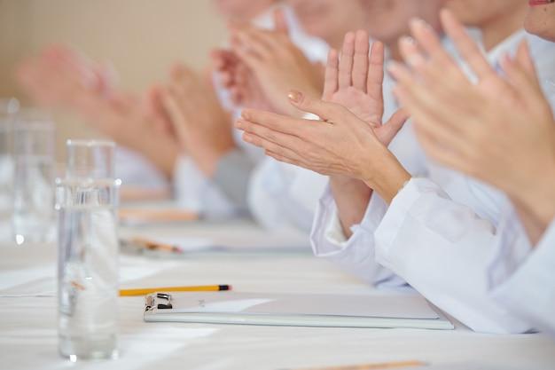 Imagem de close-up de profissionais da área médica batendo palmas após o discurso de um colega na conferência
