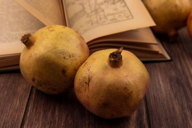 Imagem de close-up de romãs ricas em vitaminas isoladas em uma superfície de madeira