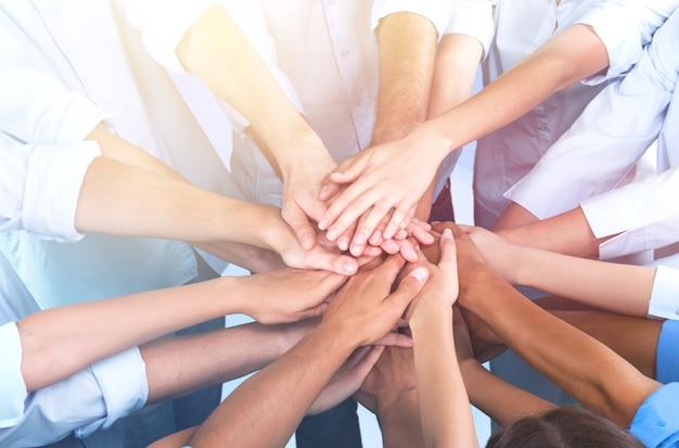 Imagem de close-up de um grupo de pessoas empilhando as mãos