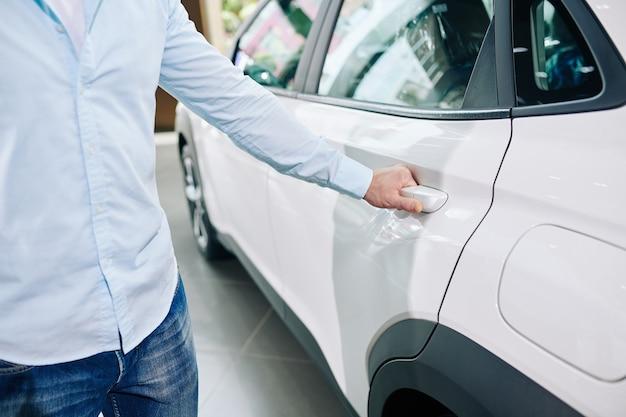 Imagem de close-up de um homem abrindo a porta traseira de um carro novo