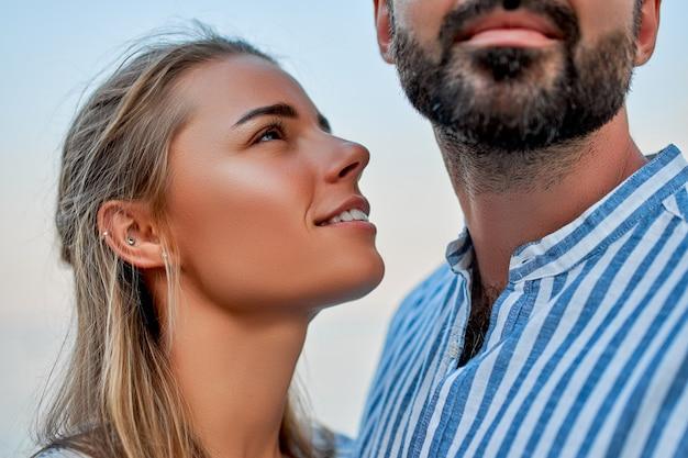 Imagem de close-up de um jovem casal apaixonado, abraçando-se contra um céu azul, romanticamente, passando um tempo curtindo um ao outro e suas férias.