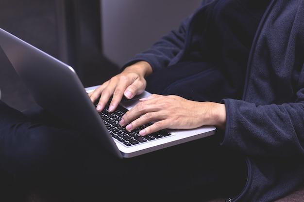 Imagem de close-up de um jovem que trabalha em seu laptop em casa.