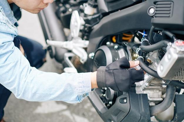 Imagem de close-up de um motociclista sério trocando canos em sua bicicleta quebrada e procurando por alguma quebra