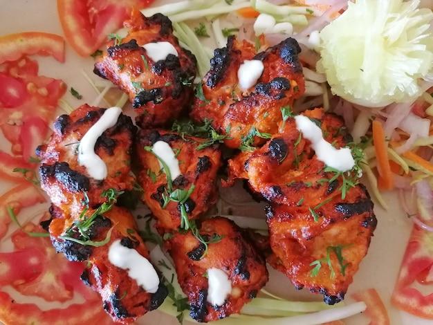Imagem de close-up de um prato indiano de frango tikka tandoori, disposto em rodelas de tomate e guarnecido com salada