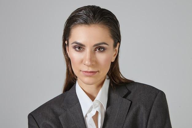 Imagem de close-up de uma mulher andrógina na moda, com maquiagem e cabelo penteado para trás, posando, vestida com uma jaqueta masculina cinza grande demais, com expressão facial séria