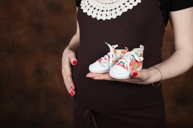 Imagem de close-up de uma mulher grávida tocando sua barriga com as mãos