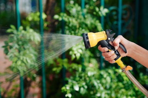 Imagem de close-up de uma mulher regando plantas e flores em seu jardim pela manhã