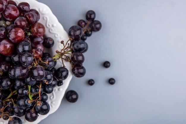 Imagem de close-up de uva preta em prato sobre pano xadrez em fundo cinza com espaço de cópia