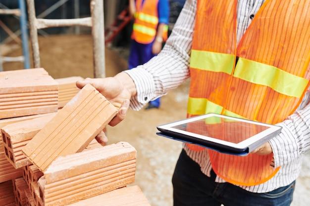 Imagem de close-up do engenheiro de construção lendo lista de materiais de construção em um tablet digital ao verificar a pilha de tijolos