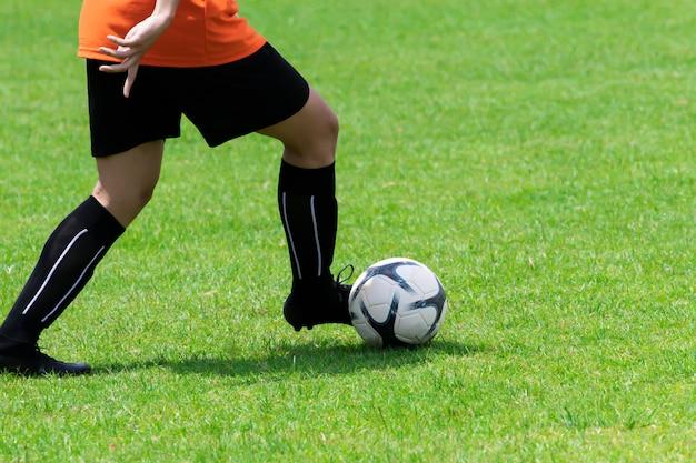 Imagem de close-up, jogadores de futebol estão driblando na grama.