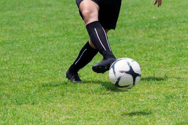 Imagem de close-up. os jogadores de futebol estão usando pés laranja, a bola está no gramado.
