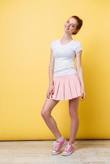 Imagem de comprimento total de atraente garota ruiva de camiseta e saia olhando