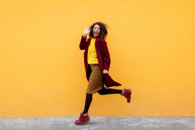 Imagem de comprimento total de mulher animada, saltando com expressão de rosto feliz em amarelo.