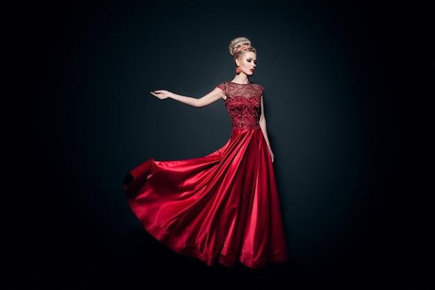 Imagem de comprimento total de uma jovem maravilhosa vestida com um vestido vermelho longo e esvoaçante com a mão levantada, sobre fundo preto.
